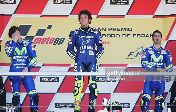 Race winner Valentino Rossi of Italy and Yamaha stands on the podium beside a disappointed 2nd placed Sete Gibernau of Spain and Honda and 3rd placed...