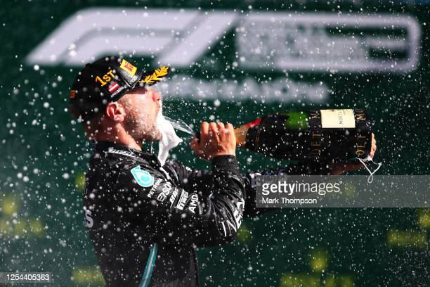 Race winner Valtteri Bottas of Finland and Mercedes GP celebrates on the podium during the Formula One Grand Prix of Austria at Red Bull Ring on July...