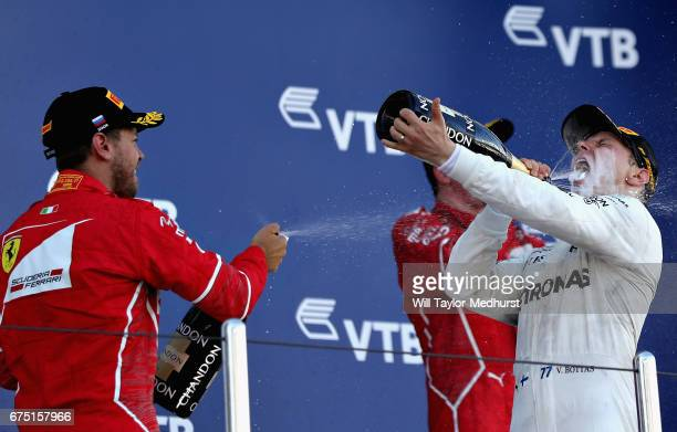 Race winner Valtteri Bottas of Finland and Mercedes GP celebrates with second placed Sebastian Vettel of Germany and Ferrari and third placed Kimi...