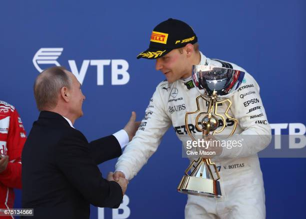 Race winner Valtteri Bottas of Finland and Mercedes GP is presented with his trophy by President of Russia Vladimir Putin during the Formula One...