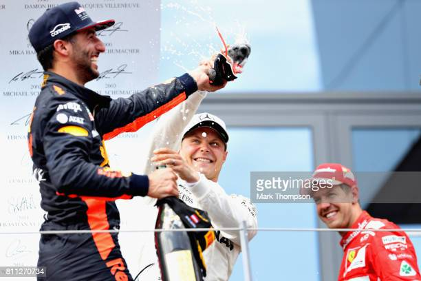 Race winner Valtteri Bottas of Finland and Mercedes GP tries to avoid doing a shoey on the podium from Daniel Ricciardo of Australia and Red Bull...