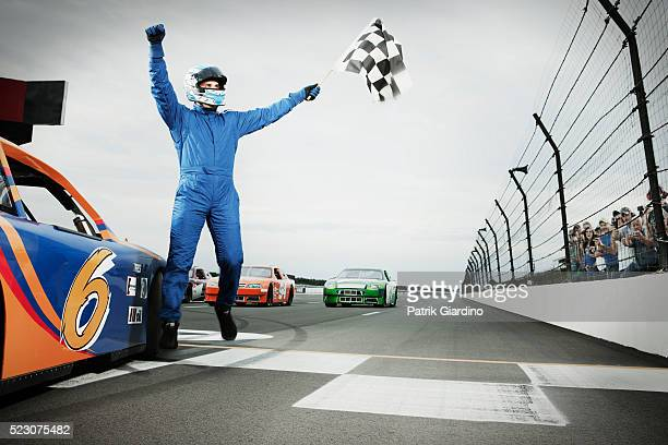 racecar driver jumping with checkered flag on sports track - nascar stock pictures, royalty-free photos & images