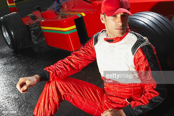 racecar driver leaning against racecar tire - will power race car driver stock pictures, royalty-free photos & images