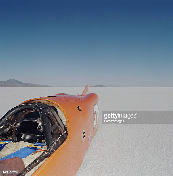 Racecar driver lying in streamliner car, elevated view