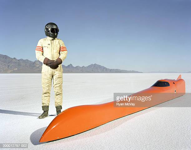 Racecar driver standing alongside streamliner car on raceway