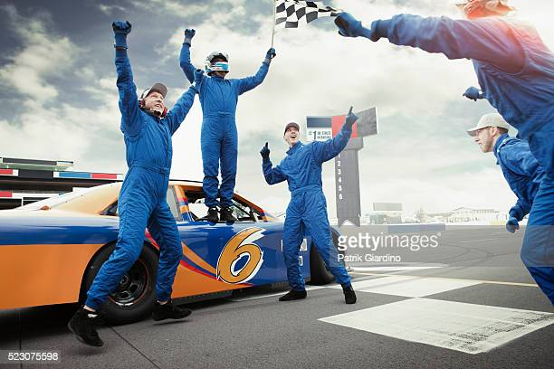 Racecar drivers jumping with checkered flag on sports track