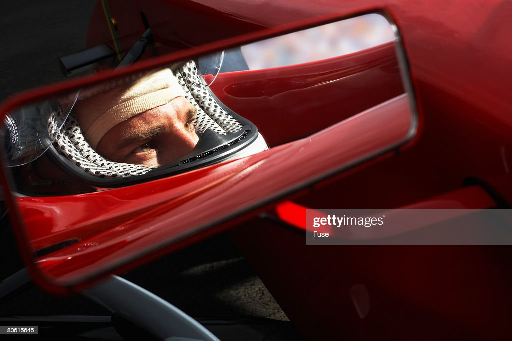 Racecar Driver's Reflection in Side-View Mirror : Stock Photo