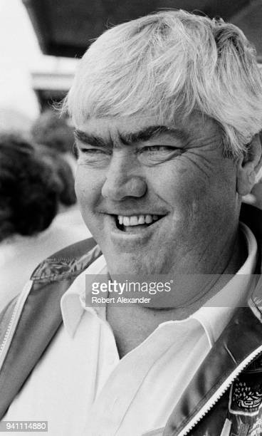 NASCAR racecar owner and former driver Junior Johnson watches his car circle the track during a practice session for the 1983 Daytona 500 stock car...