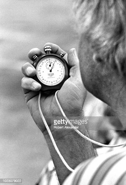 NASCAR racecar owner Junior Johnson times his racecar's speed with a stopwatch during the running of the 1981 Daytona 500 stock car race at Daytona...