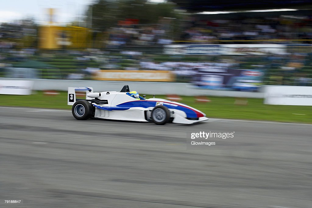 Racecar racing on a motor racing track : Stock Photo