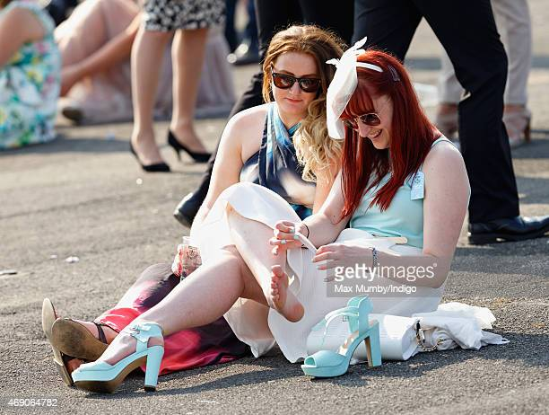 A racegoer applies a plaster to one of her feet as she attends day 1 'Grand Opening Day' of the Crabbie's Grand National Festival at Aintree...