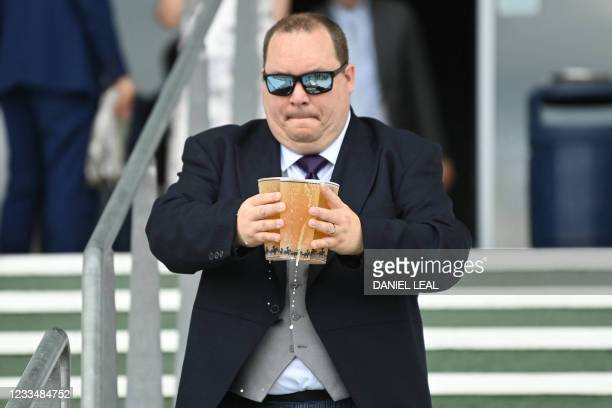 Racegoer carries beverages on the second day of the Royal Ascot horse racing meet, in Ascot, west of London on June 16, 2021. - Royal Ascot reopened...