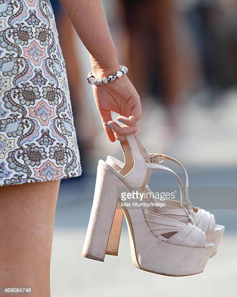 A racegoer carries her shoes as she attends day 1 'Grand Opening Day' of the Crabbie's Grand National Festival at Aintree Racecourse on April 9 2015...