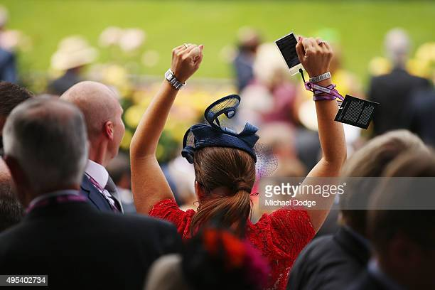 A racegoer celebrates a win in race 3 during The JB Cummings AM Tribute on Melbourne Cup Day at Flemington Racecourse on November 3 2015 in Melbourne...