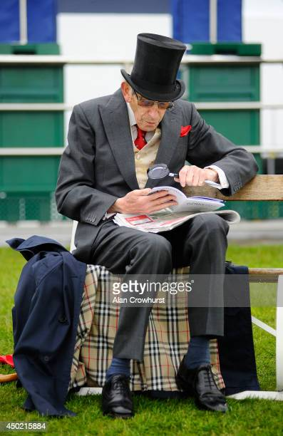 A racegoer checks the form with his magnifying glass at Epsom racecourse on June 07 2014 in Epsom England