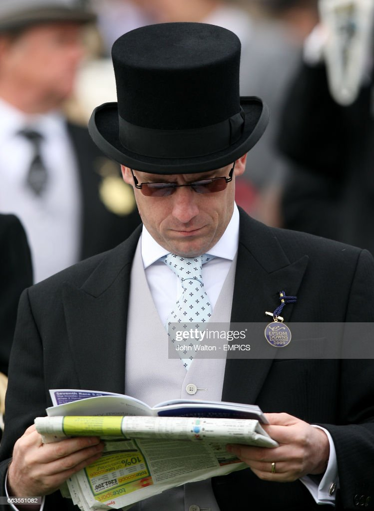 A racegoer checks the racing post for tips at Epsom Downs
