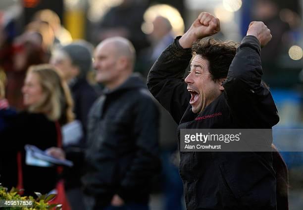A racegoer cheers a horse home at Kempton Park racecourse on November 24 2014 in Sunbury England