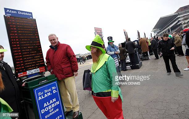 A racegoer dressed as a Leprechaun talks with a bookmaker during St Patricks Day after arriving early ahead of the second day of horse racing at the...