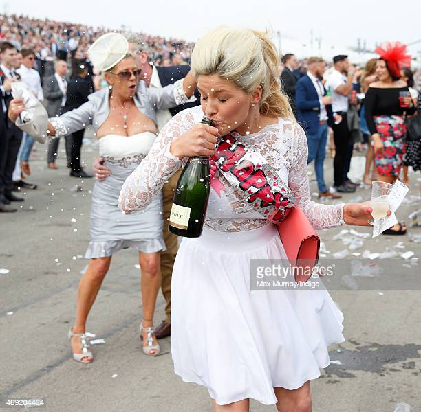 A racegoer drinks from a bottle of Champagne as she attends day 2 'Ladies Day' of the Crabbie's Grand National Festival at Aintree Racecourse on...
