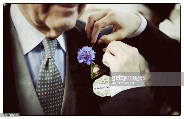 A racegoer has a flower pinned to his lapel during day one of Royal Ascot at Ascot Racecourse on June 17 2014 in Ascot England