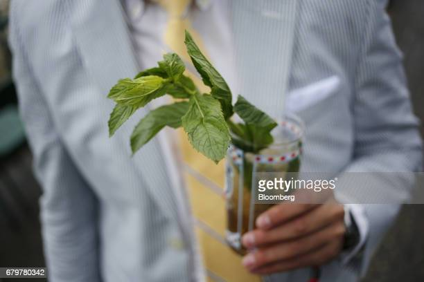 A racegoer holds a mint julep cocktail before the 143rd running of the Kentucky Derby at Churchill Downs in Louisville Kentucky US on Saturday May 6...