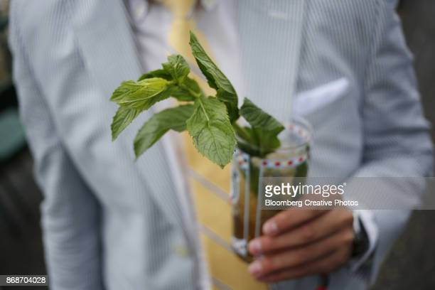 a racegoer holds a mint julep cocktail - mint julep stock pictures, royalty-free photos & images