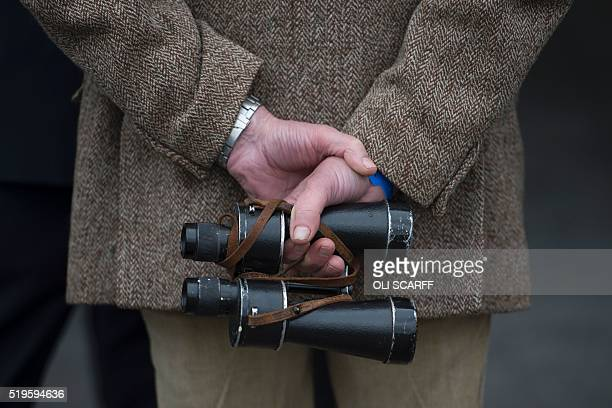 A racegoer holds a pair of binoculars as he attends the opening day of the Grand National Festival horse race meeting at Aintree Racecourse in...