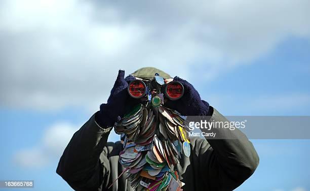 Racegoer Ian Abbots from Halifax looks through his racing badge adorned binoculars at Cheltenham Racecourse on the third day of the Cheltenham...