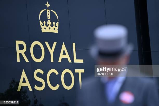 Racegoer in a top hat walks past a sign on the fifth day of the Royal Ascot horse racing meet, in Ascot, west of London on June 19, 2021. - Royal...