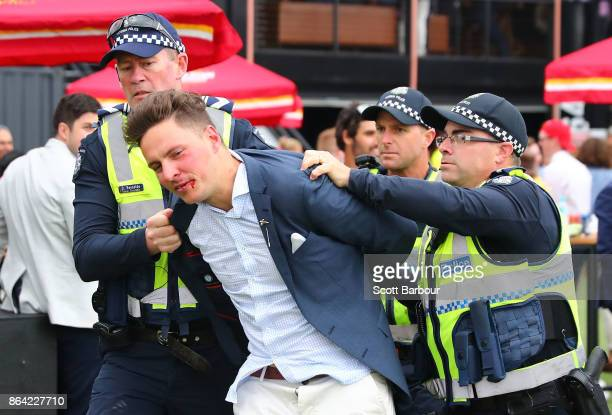 A racegoer is escorted away by police officers during Caulfield Cup Day at Caulfield Racecourse on October 21 2017 in Melbourne Australia