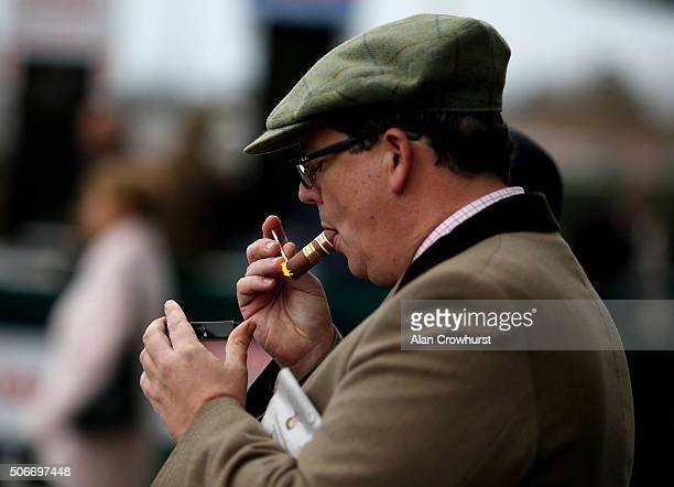 A racegoer lights up his cigar at Kempton Park racecourse on January 25 2016 in Sunbury England