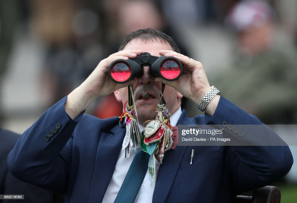 A racegoer looks through his binoculars during Champion Day of the 2017 Cheltenham Festival at Cheltenham Racecourse.