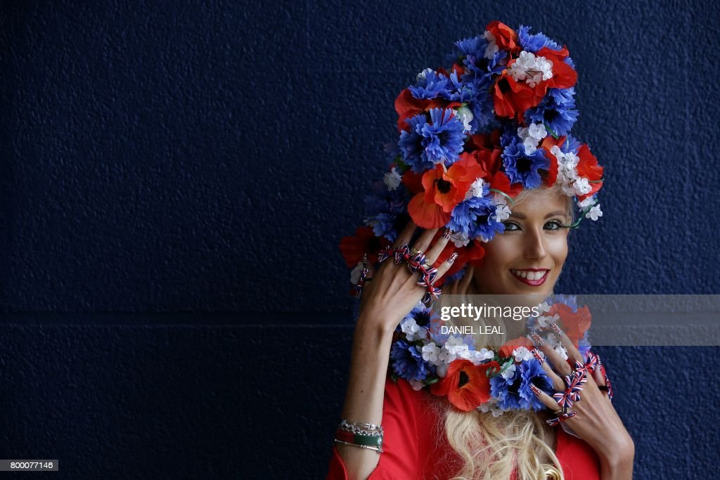 TOPSHOT - Racegoer Natalia Beach, dressed in a Union Flag themed outfit, poses for a photgraph as she arrives to attend the fourth day of the Royal Ascot horse racing meet, in Ascot, west of London, on June 23, 2017. The five-day meeting is one of the highlights of the horse racing calendar. Horse racing has been held at the famous Berkshire course since 1711 and tradition is a hallmark of the meeting. Top hats and tails remain compulsory in parts of the course while a daily procession of horse-drawn carriages brings the Queen to the course. / AFP PHOTO / Daniel LEAL