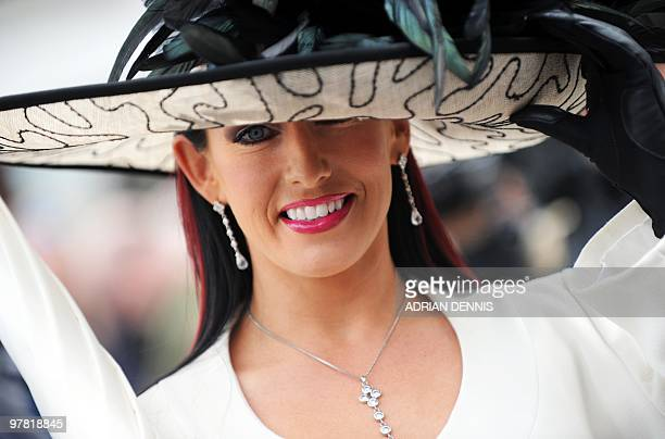 A racegoer poses for a photograph as she arrives for Ladies Day ahead of the third day of horse racing at the Cheltenham Festival on March 18 2010...