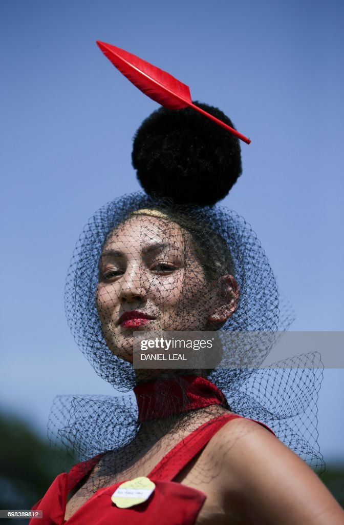 A racegoer poses for a photograph as they arrive on day one of the Royal Ascot horse racing meet, in Ascot, west of London, on June 20, 2017. The five-day meeting is one of the highlights of the horse racing calendar. Horse racing has been held at the famous Berkshire course since 1711 and tradition is a hallmark of the meeting. Top hats and tails remain compulsory in parts of the course while a daily procession of horse-drawn carriages brings the Queen to the course. / AFP PHOTO / Daniel Leal-Olivas