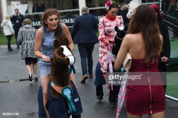 A racegoer poses for a picture on a hobby horse during Ladies Day of the Grand National Festival horse race meeting at Aintree Racecourse in...
