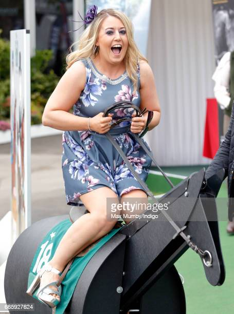 A racegoer rides a mechanical race horse simulator as she attends day 2 'Ladies Day' of the Randox Health Grand National Festival at Aintree...