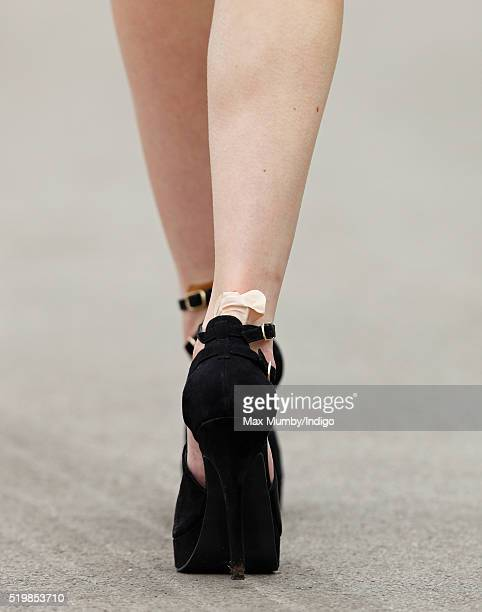 A racegoer seen wearing a sticking plaster on her heel as she attends day 2 'Ladies Day' of the Crabbie's Grand National Festival at Aintree...