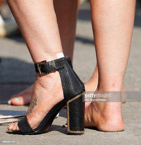 A racegoer seen wearing only one of her shoes as she attends day 1 'Grand Opening Day' of the Crabbie's Grand National Festival at Aintree Racecourse...