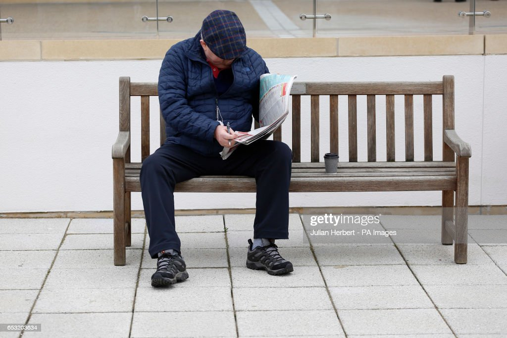 A racegoer studies the form during Champion Day of the 2017 Cheltenham Festival at Cheltenham Racecourse.