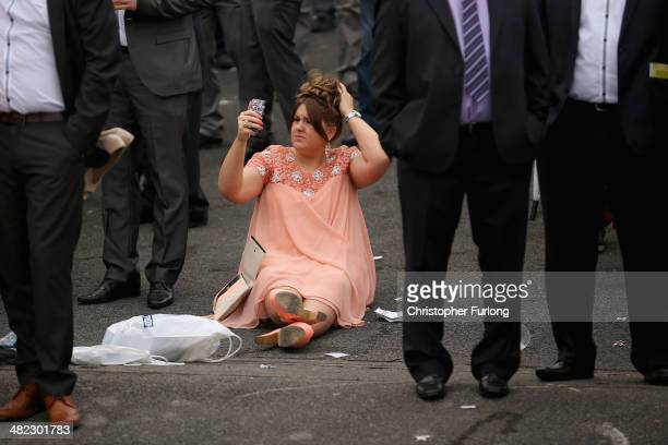 A racegoer uses the camera on her phone to check her hair on the opening day of the Grand National Festival at Aintree Racecourse on April 3 2014 in...