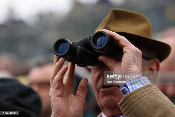 A racegoer watches a race through binoculars during Gold Cup day at the Cheltenham Festival at Cheltenham Racecourse on March 18 2016 in Cheltenham...
