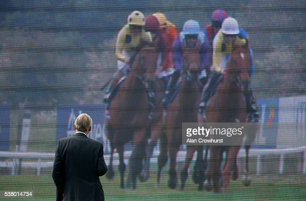 Racegoer watches the action on a big screen at Epsom Racecourse on June 4, 2016 in Epsom, England.