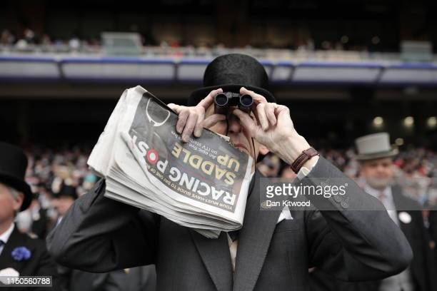 A racegoer watches the action through some binoculars on the first day of races at Ascot Racecourse on June 18 2019 in Ascot England The fiveday...