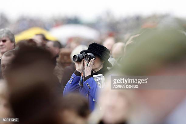 Racegoer watches the horse racing through binoculars during the fourth day of the Cheltenham Festival on March 14, 2008. The highlight of the...