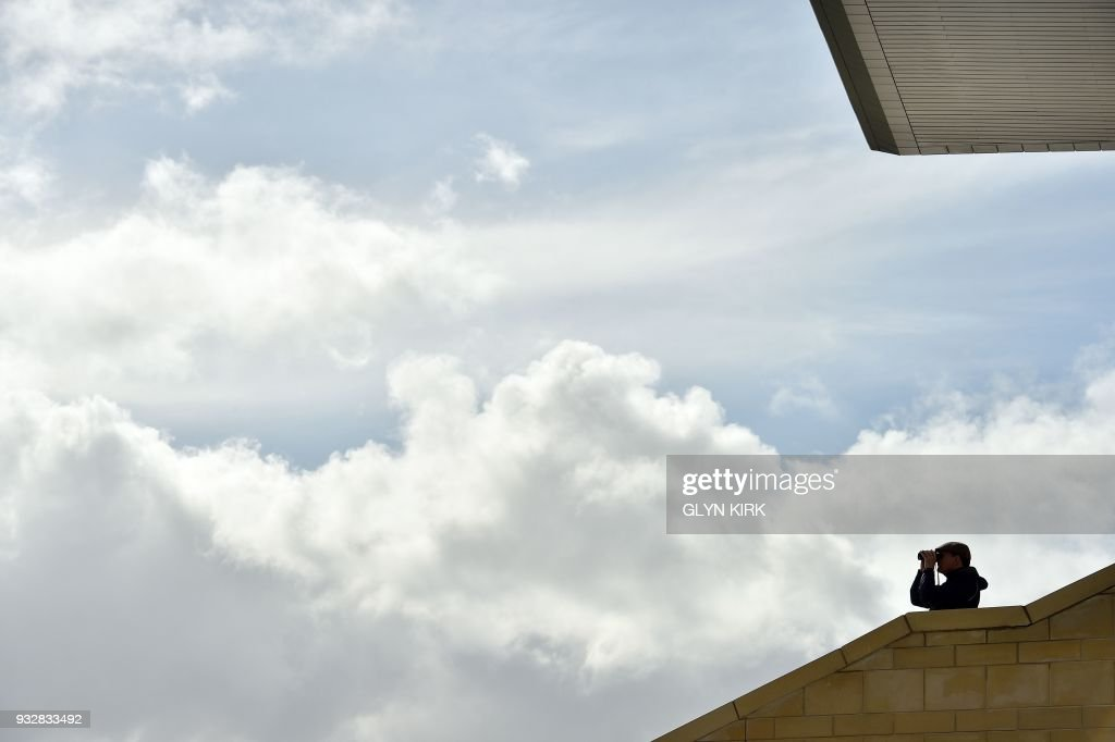 A racegoer watches the proceedings through a pair of binoculars from the grandstand on the final day of the Cheltenham Festival horse racing meet at Cheltenham Racecourse in Gloucestershire, south-west England, on March 16, 2018. KIRK