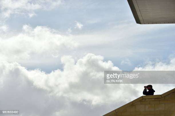 A racegoer watches the proceedings through a pair of binoculars from the grandstand on the final day of the Cheltenham Festival horse racing meet at...