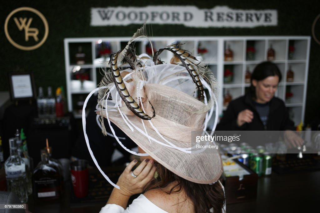 A racegoer wears a derby hat while waiting at the Woodford Reserve whiskey bar on the afternoon of the 143rd running of the Kentucky Derby at Churchill Downs in Louisville, Kentucky, U.S., on Saturday, May 6, 2017. The 143rd running of the Kentucky Derby will feature a field of twenty horses with the winner receiving a gold trophy plus an estimated $1.24 million payday. Photographer: Luke Sharrett/Bloomberg via Getty Images