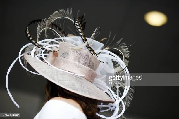 A racegoer wears a derby hat while waiting for a bourbon cocktail on the afternoon of the 143rd running of the Kentucky Derby at Churchill Downs in...
