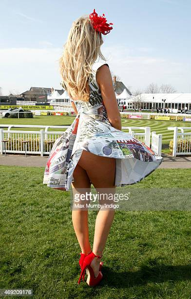 A racegoer wears a dress with a newspaper cuttings design as she attends day 2 'Ladies Day' of the Crabbie's Grand National Festival at Aintree...